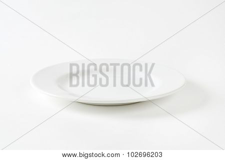 Empty white porcelain dinner plate with rolled edge