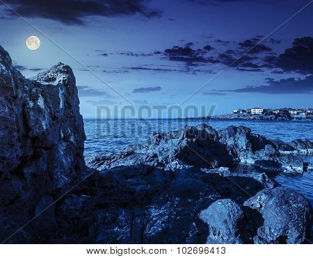 Sea Bay With Boulders And Old City At Night
