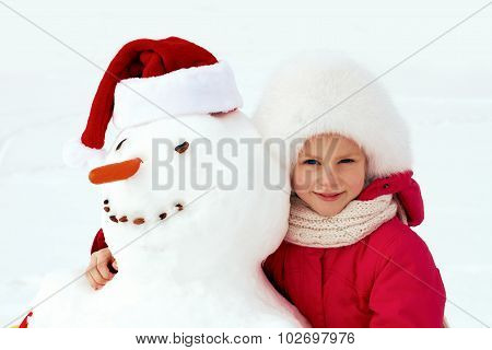 Little Girl Hugging A Snowman And Laughs. Winter Fun