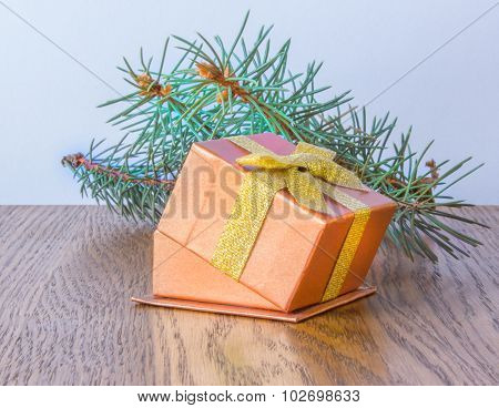 Red Gift Box With Gold Bow And Christmas Tree Branch On The Table