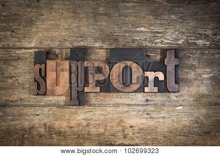 Support, set with vintage letterpress printing blocks on wooden background