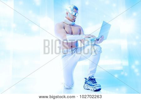 Handsome muscular man of the future wearing futuristic glasses working on a laptop. Technologies of the future.