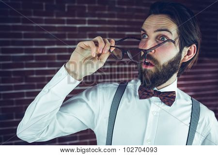 Fearful man holding eyeglases while looking away against brick wall