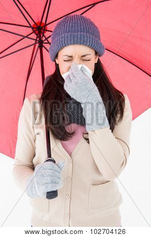 Sick brunette blowing her nose while holding an umbrella on white background