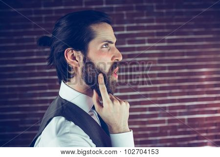 Side view of hipster with hand on chin thinking against brick wall