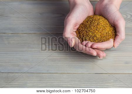 Woman showing handful of milled seed in close up