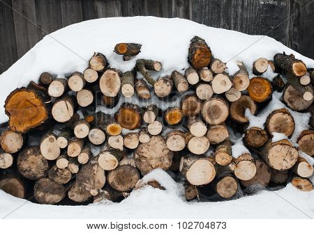 Stack Of  Snowy Firewood On  Wooden Background