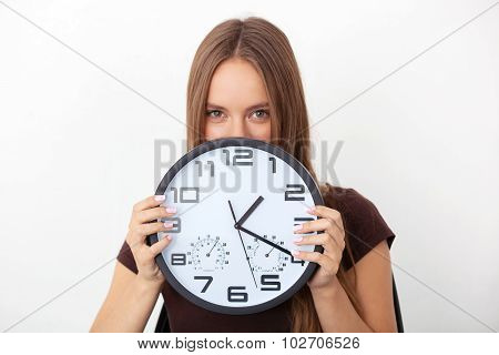 Young Woman Holding Big Wall Clocks On White Background.