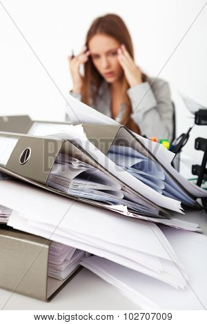 Portrait Of Beautiful Business Woman Surrounded By Big Pile Of Documents.