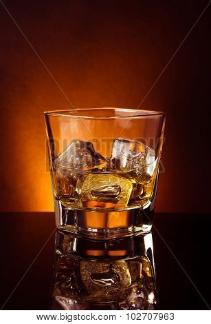 Glass Of Whiskey On Black Table With Reflection, Warm Tint Atmosphere