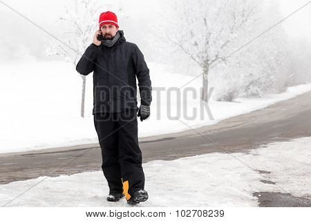 Man With Mobile Phone Is Walking Across A Icy Street