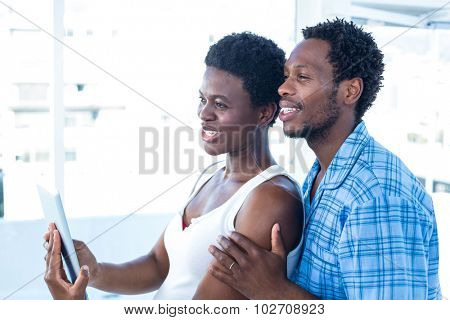 Happy couple looking away while holding digital tablet