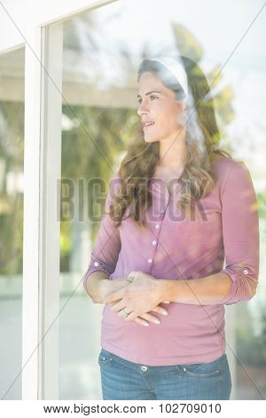 Happy pregnant woman standing by glass window at home