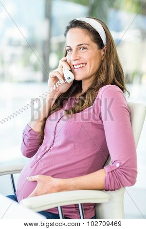 Happy pregnant businesswoman on phone call sitting at home office