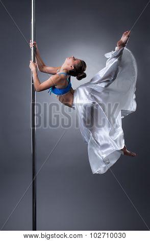 Sexy dancer turning gracefully around pole