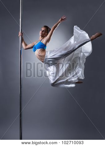 Studio shot of graceful woman turning around pole