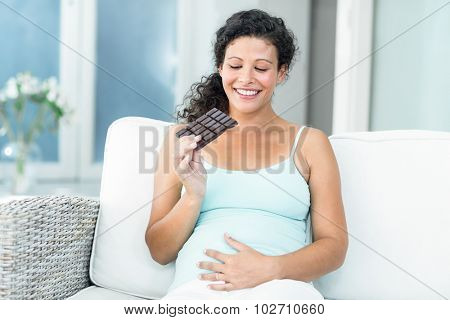 Happy pregnant woman looking at chocolate bar while sitting on sofa