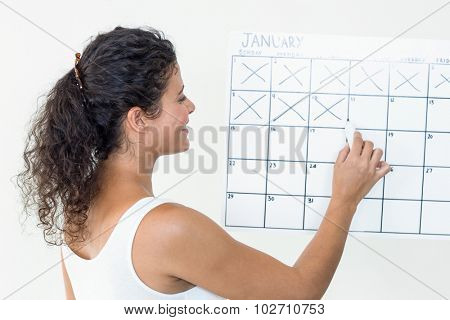 Smiling pregnant woman marking off dates on calendar against white background