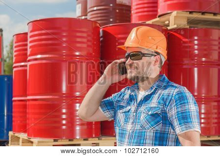 Worker in safety helmet standig in front of metal barrels