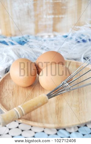 Eggs With Whisk On Wooden Plate