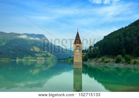 Beautiful view of the lake Resia. Famous tower in the water. Alps, Italy, Europe.