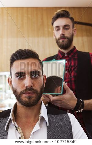 young hipster barber shows haircut to a customer