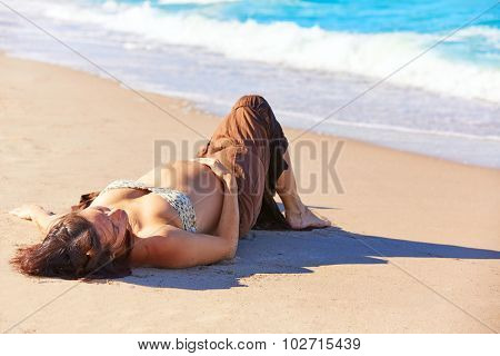 Beautiful pregnant woman on the beach lying on sand