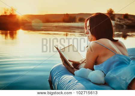 Pretty Woman Is Laying On The Floating Bed And Reading A Book. Summer Sunset On The Background.