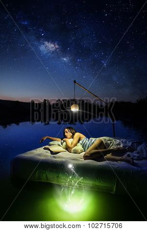 Pretty Woman Is Laying On The Floating Bed And Reading A Book. Summer Sky Full Of Stars On The Backg