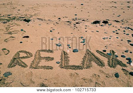 Holidays background with word RELAX on a sandy beach