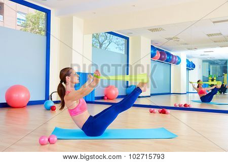 Pilates woman teaser rubber band exercise workout at gym indoor