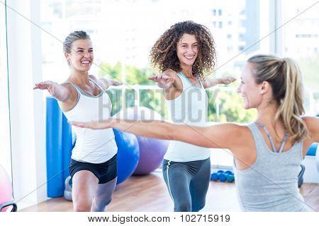 Smiling women doing warrior II pose in fitness studio