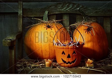 Pumpkins and spiders with candles on bench at night