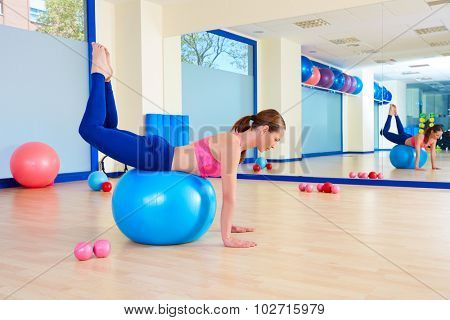 Pilates woman fitball rocking exercise workout at gym indoor