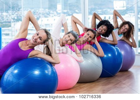 Smiling women stretching on exercise balls with hands behind head in fitness studio