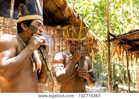 Native Brazilian men playing wooden flute at an indigenous tribe in the Amazon