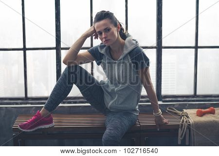 Woman Resting Elbow On Knee And Head On Hand On Gym Bench