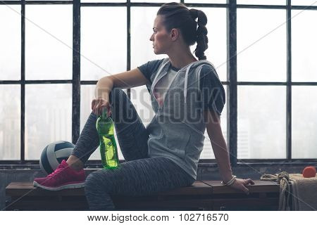 Woman In Workout Gear Sitting On Bench In City Loft Looking Out