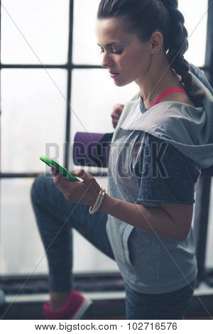 Fit Woman In Exercise Gear In Loft Gym Looking Down At Phone