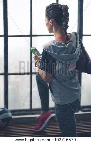 Rear View Of Woman Holding Mobile Phone Near Window In Loft Gym