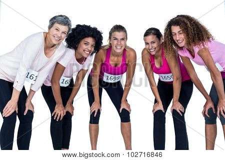 Portrait of smiling athletes bending while standing against white background