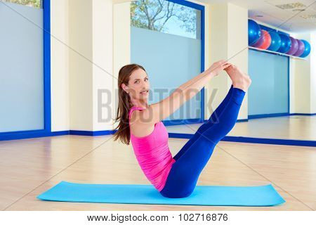Pilates woman open leg rocker exercise workout at gym indoor
