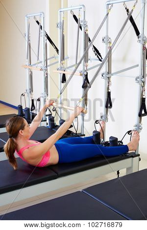 Pilates reformer woman roll up exercise workout at gym indoor