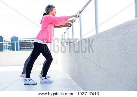 Women leaning on railing while exercising outdoors