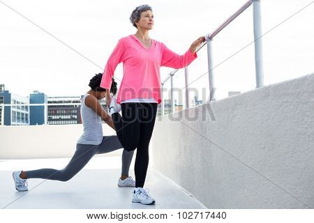 Mature woman exercising with female friend by railing outdoors