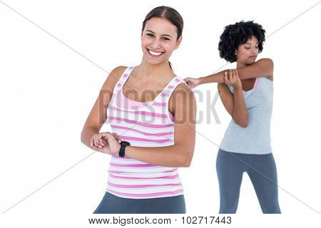 Portrait of cheerful woman wearing wristwatch while female friend exercising against white background