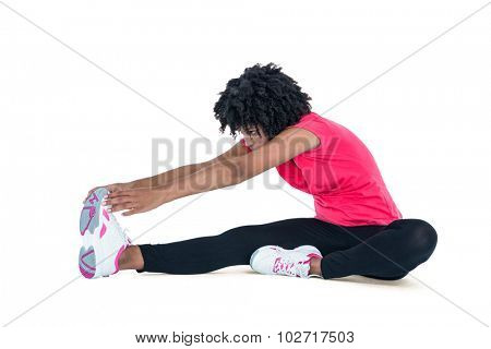 Young woman touching toes while exercising against white background