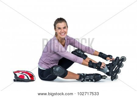 Portrait of happy woman wearing inline skates while sitting over white background