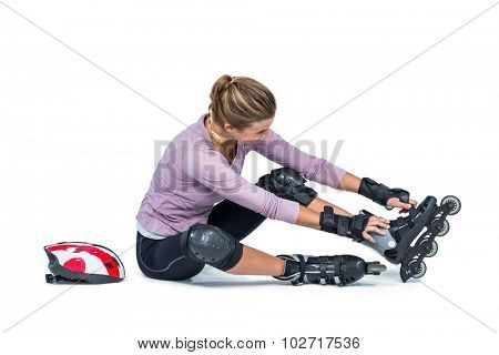 Woman wearing inline skates while sitting over white background