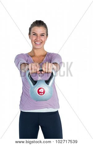 Portrait of happy woman exercising with kettlebell against white background